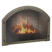 Arched glass fireplace doors with forged iron frame over a wood burning fire