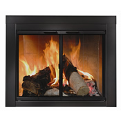 Angled image of stacked wood logs in front of glass fireplace door with black frame in brick hearth