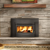 Black wood burning fireplace insert in the stone hearth of a living room