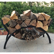 Black metal firewood rack holding wood logs and standing on an outdoor patio