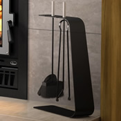 Ultra modern iron fireplace tool set with a shovel, broom, and tongs suspended from a wrought iron stand