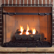 Mesh fireplace screen standing in front of a wood burning fireplace with a warm fire inside