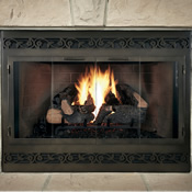 Glass fireplace door with black trim covering a fireplace with blazing gas logs inside
