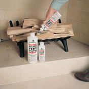 A hand dowsing wood logs with a bottled fire starter